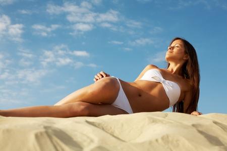 Image of female in white bikini sunbathing on sandy beach