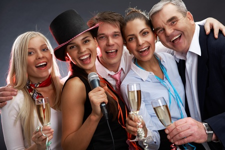 Photo of businesspeople with flutes of sparkling champagne singing Christmas songs