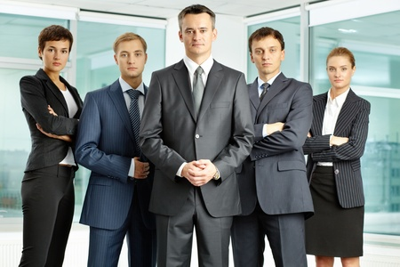 Portrait of serious business group looking at camera with confident man at foreground