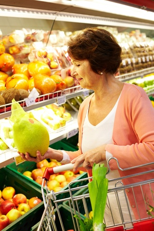 Photo pour Image of senior woman choosing products in supermarket with cart near by - image libre de droit