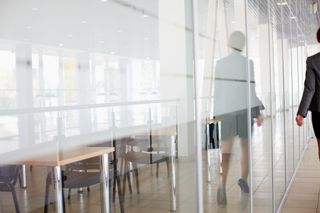 Reflection of businesswoman walking along the office corridor