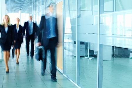 Foto de Blurred figures of business people walking along the corridor  - Imagen libre de derechos