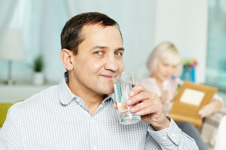 Portrait of happy senior man drinking water from glass and his wife reading book behind
