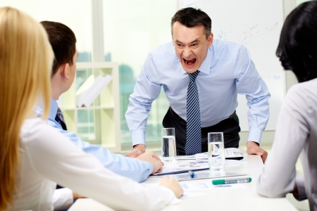 Angry businessman shouting at his workers with an expressive look