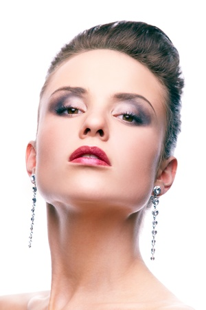 Gorgeous woman with long earrings looking at camera