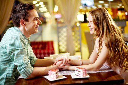 A young happy couple sitting in restaurant and looking at one another