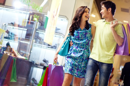 Photo pour Casually dressed beautiful couple walking through the mall carrying a lot of shopping bags - image libre de droit