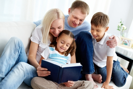 Photo for Portrait of happy family with two children reading book  - Royalty Free Image