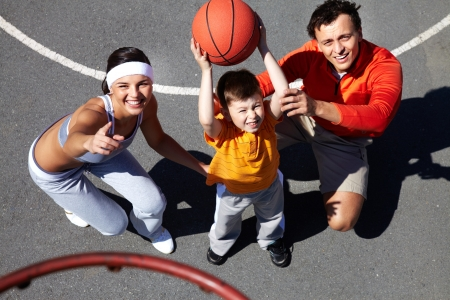 Image of parents showing their son how to throw ball into basket