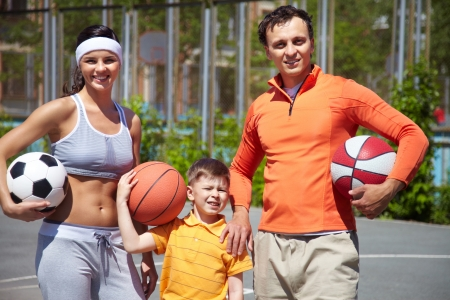 Image of parents and their son holding different balls