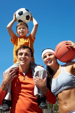 Portrait of happy family holding balls outside