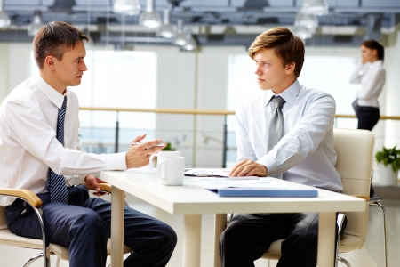 Male business people of different age having a serious conversation
