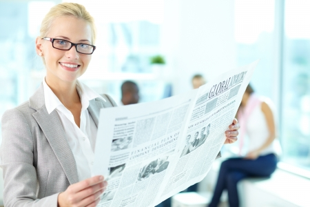 Portrait of happy female with newspaper looking at camera in working environment