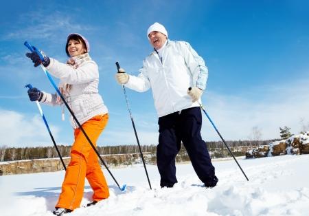 Portrait of mature couple skiing outside