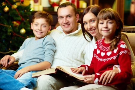 Portrait of friendly family with book looking at camera on Christmas evening