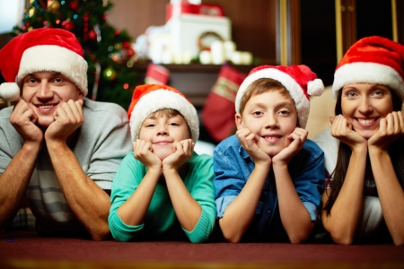 Portrait of friendly family in Santa caps looking at camera on Christmas evening