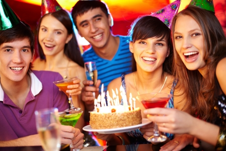 Portrait of joyful friends toasting and looking at camera at birthday party