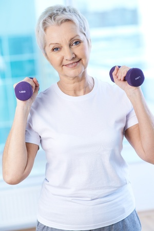 Photo pour Portrait of pretty senior woman exercising with dumbbells  - image libre de droit