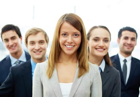 Foto de Happy businesswoman looking at camera with smart associates behind - Imagen libre de derechos