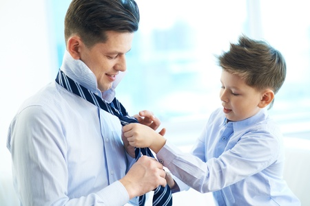 Foto de Photo of little boy helping his father tie necktie - Imagen libre de derechos