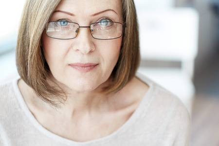 Mature woman in eyeglasses looking at camera