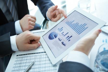Foto de Close-up of business partners discussing document in touchpad - Imagen libre de derechos