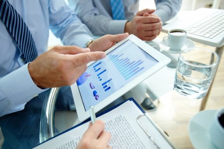 Foto de Modern people doing business, graphs and charts being demonstrated on the screen of a touchpad - Imagen libre de derechos