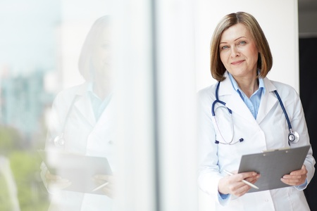 Photo for Copy-spaced portrait of a friendly general practitioner holding a medical record - Royalty Free Image