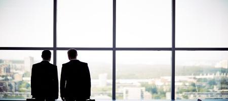 Foto de Silhouettes of two businessmen standing by the window - Imagen libre de derechos