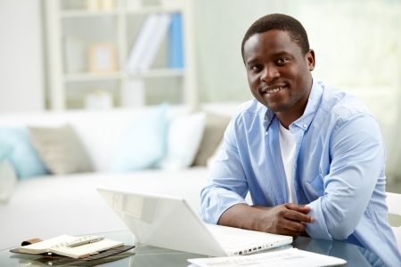 Foto de Image of young African man looking at camera with laptop near by - Imagen libre de derechos