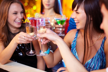 Photo pour Portrait of joyful friends toasting at birthday party with focus on laughing girl - image libre de droit