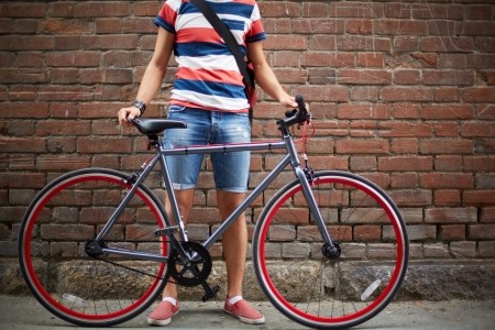 Photo pour Close-up of guy with bicycle against brick wall - image libre de droit