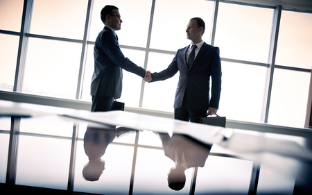 Photo pour Silhouettes of two businessmen standing by the window and handshaking - image libre de droit
