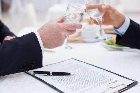 Foto de Close up of business partners clinking glasses after a concluded deal - Imagen libre de derechos