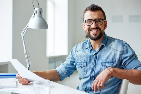 Photo pour Smiling businessman in denim shirt and eyeglasses looking at camera in office - image libre de droit