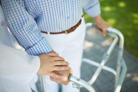Photo pour Close-up of clinician hand on that of disabled woman - image libre de droit