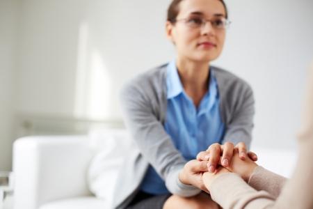 Foto de Image of psychiatrist holding hands of her patient - Imagen libre de derechos