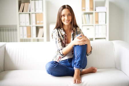 Happy girl in casual clothes sitting on sofa