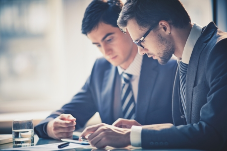 Foto per Image of two young businessmen using touchpad at meeting - Immagine Royalty Free