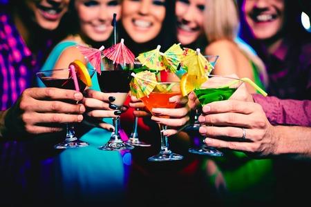 Photo pour Glasses with cocktails held by happy friends at party - image libre de droit