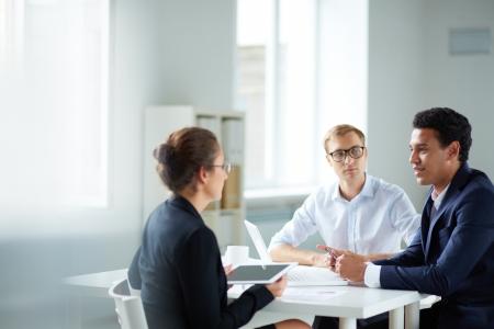 Photo pour Portrait of smart business partners communicating at meeting - image libre de droit
