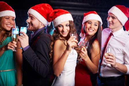 Photo pour Company of friends in Santa caps holding flutes of champagne at Christmas party - image libre de droit