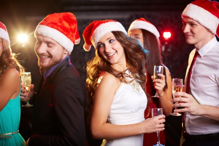 Photo pour Company of friends in Santa caps holding flutes of champagne while dancing at Christmas party - image libre de droit