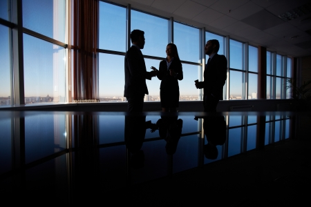Photo pour Outlines of three office workers interacting by the window - image libre de droit