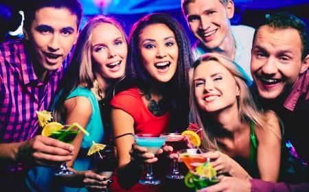 Photo pour Group of happy friends with cocktails toasting at party - image libre de droit