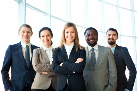 Foto de Group of business partners looking at camera with smiles, pretty leader in front - Imagen libre de derechos
