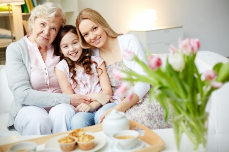 Photo for Portrait of happy little girl, her mother and grandmother looking at camera at home - Royalty Free Image