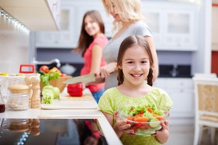 Foto de Portrait of happy girl with vegetable salad on background of her mother and sister cooking - Imagen libre de derechos