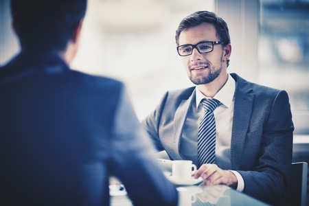 Photo pour Image of young businessman with cup of coffee communicating with his colleague - image libre de droit