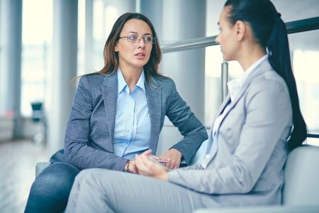 Photo pour Image of two businesswomen sitting and discussing new ideas - image libre de droit